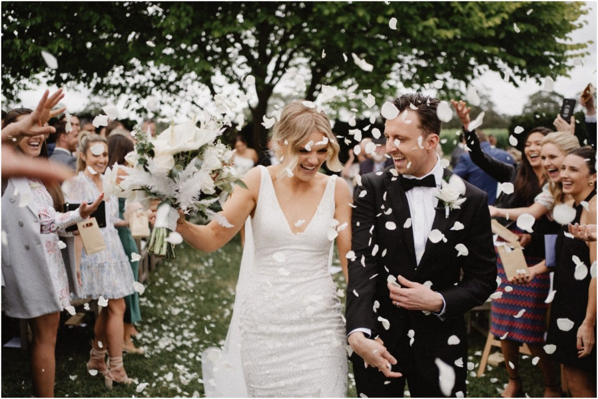 A bride and groom get showered with confetti as they walk back down the aisle at their Centennial Vineyards Restaurant Wedding