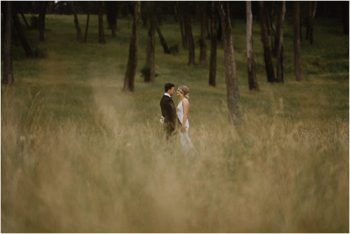 A newly married couple stand in long grass during their Centennial Vineyards Restaurant wedding
