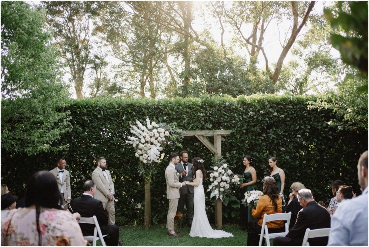 A beautiful Merribee wedding ceremony with a wooden arbor and some lovely flowers.