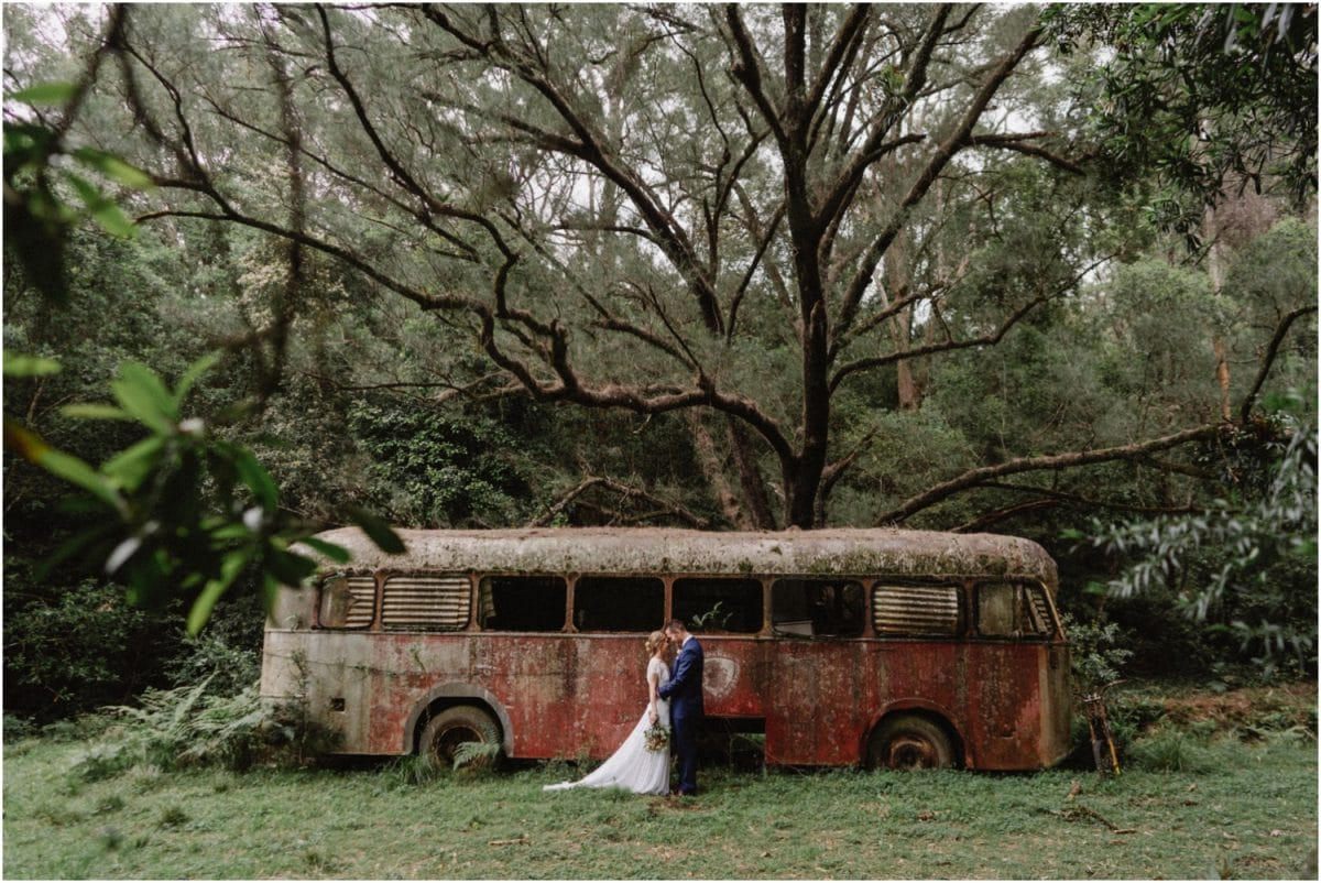 A newly married couple stand in front of an abandoned bus at their Kangaroo Valley elopement